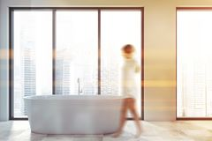 Woman walking in bathroom with tub. Young woman walking in minimalistic bathroom with white walls, tiled floor, large windows with cityscape and comfortable royalty free stock photo