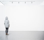 Young woman walking in modern gallery and looking at the blank canvas. Square Stock Images
