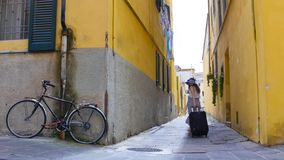 A young woman walking through the narrow yellow streets with luggage stock images
