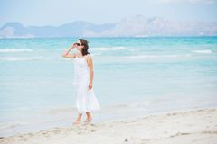 Young woman walking near blue sea. Royalty Free Stock Photo