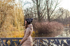 Young woman walking near lake in park in autumn Stock Photography
