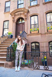 Young woman walking near old houses in historic. Old houses with stairs in historic district of West Village Royalty Free Stock Photography