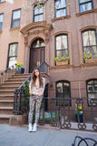 Young woman walking near old houses in historic. Old houses with stairs in historic district of West Village Stock Image