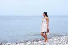 A young woman walking near the sea Stock Image