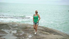 Young woman walking near sea. Young blonde woman walking near sea on rocks stock video