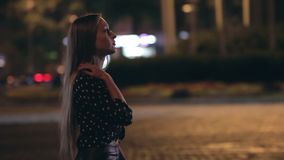 Young woman walking through a night city street stock video