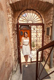 Young woman walking in old forged gates and narrow street Royalty Free Stock Photos