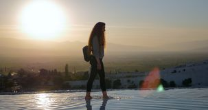 Young woman walking in Pamukkale terraces. Young smiling woman walking in Cotton Castle limestone terraces in Pamukkale Turkey during beautiful sunset stock video