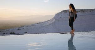 Young woman walking in Pamukkale terraces. Young smiling woman walking in Cotton Castle limestone terraces in Pamukkale Turkey during beautiful sunset stock footage