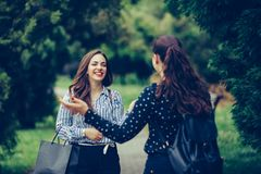 Young woman walking in a park and accidentally meeting her best friend stock image
