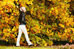 Young woman walking in park in the autumn Stock Photo