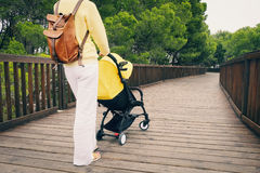 Young woman walking in park with baby stroller. Mother strolling with newborn in carriage. Young woman walking in park with baby stroller Stock Photo