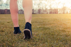 Young woman walking in the park. Closeup on a woman's feet as she is walking in the park on the grass Royalty Free Stock Image