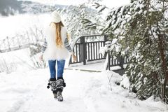 Young woman walking at park covered with snow Stock Photo