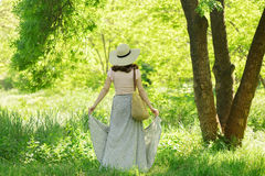 Young woman is walking in a park in hat and a long skirt with a Royalty Free Stock Photo
