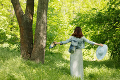 Young woman is walking in a park in hat and a long skirt with a Stock Photo