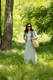 Young woman is walking in a park in a long skirt with a floral p Royalty Free Stock Photos