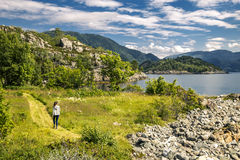 Young woman walking in the park, Norway. Young woman walking in the park next to the fjord, Norway Stock Images