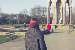 Young woman walking in a park. A young woman is walking in a park on a sunny winter day near a monument Royalty Free Stock Photo