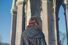 Young woman walking in a park. A young woman is walking in a park on a sunny winter day near a monument Royalty Free Stock Photos
