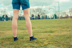 Young woman walking in the park. And watching kids play basketball Stock Photo