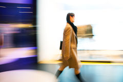 Young woman walking past shop front window Stock Image
