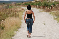 Young woman walking on path in the field. In Antequera, Andalusia, Spain Royalty Free Stock Images