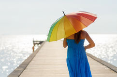 Young woman walking on the pier with umbrella.  Royalty Free Stock Photography