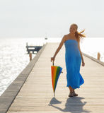 Young woman walking on the pier with umbrella Royalty Free Stock Image