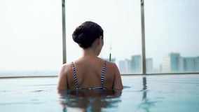Young woman walking in pool with cocktail stock footage