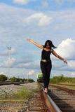 Young woman walking on a railroad Stock Photo