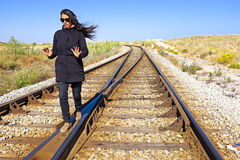 Young woman walking on a railroad track Royalty Free Stock Photography