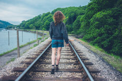 Young woman walking on railroad tracks Royalty Free Stock Photo