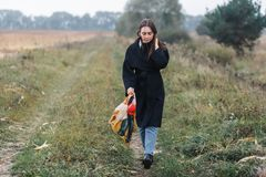 Young woman walking on the road in the village. rainy autumn weather. Sad mood.  stock photography