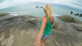 Young woman walking on rocky beach holding man hand. Young blonde woman walking on rocky beach holding man hand stock video footage