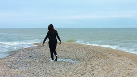 Young woman walking on sandy beach on background sea wave and splash. Young woman walking on sandy beach enjoying sea wave and splash back view. Carefree woman stock footage