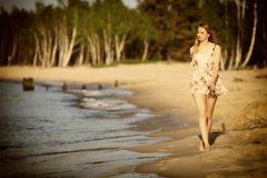 Young woman walking on a sandy beach Royalty Free Stock Images