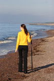 Young woman walking on a seaside. Young woman with wooden stick walking on a seaside Royalty Free Stock Photography