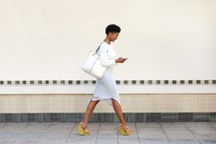 Young woman walking and sending text message on cell phone. Full length side portrait of a young woman walking and sending text message on cell phone Royalty Free Stock Photography