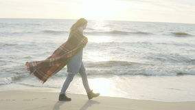 Young woman walking on shore of the sea. Pensive female with plaid spending time alone on the beach in windy cold day. stock footage
