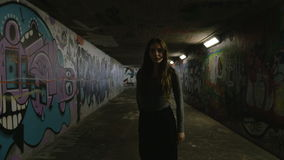 Young Woman Walking in and Slowly Dancing Underground Passageway. A young woman casually walks and dances in an underground passageway towards the camera. The stock video footage