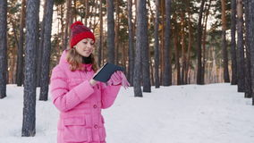 Young woman walking on a snow-covered forest, checks its way across the tablet stock video footage