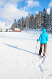 Young woman walking with snowshoes on fresh snow Stock Image