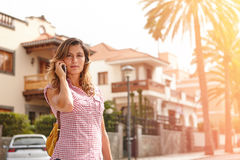 Young woman walking while speaking on cell phone Royalty Free Stock Image