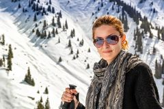 Young woman with walking sticks in mountains. Young woman with walking sticks on a background of snow-capped mountains Royalty Free Stock Images