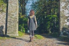 Young woman walking through stone entrance Stock Photo