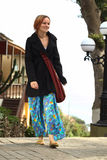 Young Woman Walking on the Street. Young woman wearing colorful pants and a black coat walking on the street Stock Image