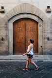 Young woman walking on the street against old arch door. In Florence Royalty Free Stock Photo