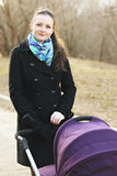 Young woman walking with stroller. In a park Royalty Free Stock Photo