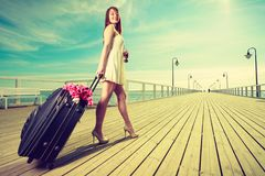 Young woman walking with suitcase on wheels Royalty Free Stock Photography